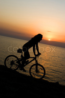 Men rides his bike on the sunset