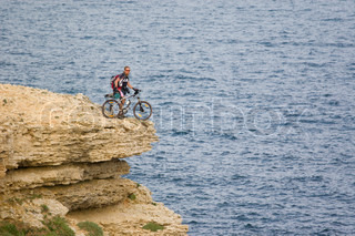 Men with his bike, on the top of the sea, shot on 200 mm optics.