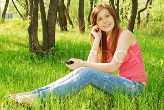 beautiful teenagerl listening to music in ear-phones in park