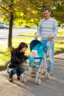 Happy family outdoor - mother, father and dauther are smiling in baby carriage