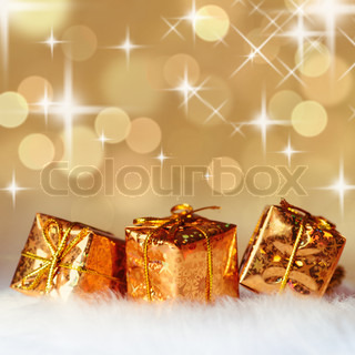 Gold Christmas presents on white fur and background of defocused golden lights. Shallow DOF.