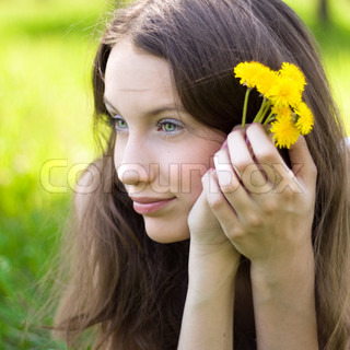 young beautiful teenager with dandelion bouquet