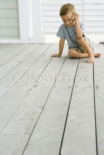 ©Laurence Mouton/AltoPress/Maxppp ; Boy sitting on deck listening to seashell