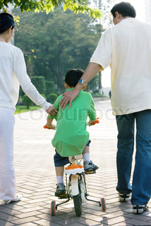 ©James Hardy/AltoPress/Maxppp ; Boy riding bicycle with training wheels, parents on either side, rear view