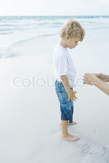 ©Sigrid Olsson/AltoPress/Maxppp ; Boy standing on beach with parent