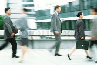 ©James Hardy/AltoPress/Maxppp ; Male and female professionals walking on sidewalk, blurred motion