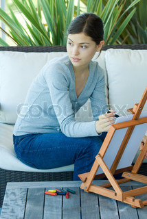 ©Odilon Dimier/AltoPress/Maxppp ; Young woman sitting with easel, drawing with pastels