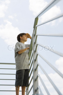 ©Laurence Mouton/AltoPress/Maxppp ; Boy standing on balcony, looking at view, low angle view