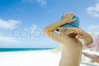 ©Sigrid Olsson/AltoPress/Maxppp ; Mother putting sunscreen on child at beach