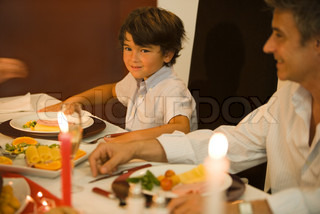 ©Sigrid Olsson/AltoPress/Maxppp ; Man and boy sitting at dinner table, smiling