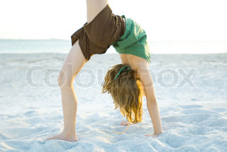 ©Michèle Constantini/AltoPress/Maxppp ; Girl doing gymnastics on beach