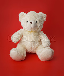 White generic teddy bear sitting on red