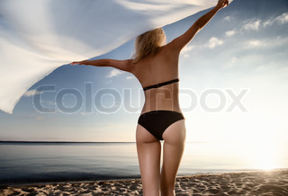 young gorgeous caucasian blonde model posing at sunset on the beach