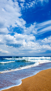 Sandy shore and white clouds on blue sky background.