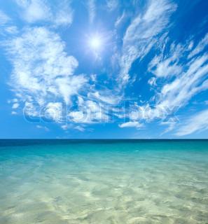Blåt hav og sol på himlen med skyer