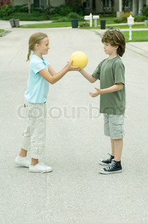 ©Odilon Dimier/AltoPress/Maxppp ; Girl handing boy ball in residential street