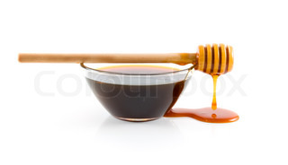 Wooden honey lifter and glass bowl of honey on a white background.