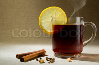 Hot drink with lemon on a fabric background.