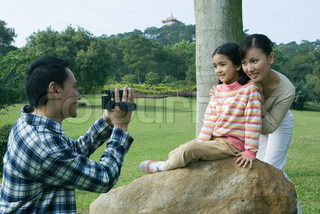 ©James Hardy/AltoPress/Maxppp ; Man filming wife and daughter in park with video camera