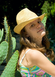 The nice girl in a straw hat smiles near a cactus.