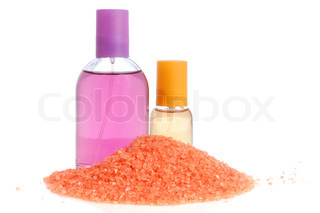 Perfume in bottle, lotion and pink salt over white background