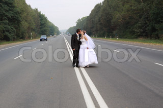 wedding couple kissing on the road