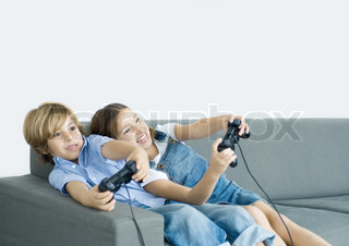 ©Matthieu Spohn/AltoPress/Maxppp ; Boy and girl playing video game, holding out joysticks on sofa