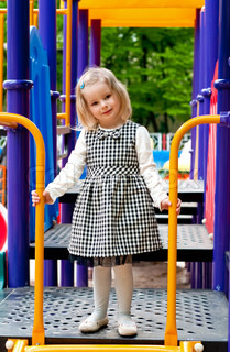 A 3 year old girl in playground equipment
