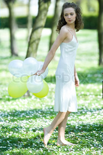 ©Rafal Strzechowski/Agence FREE Rafal Strzechowski/AltoPress/Maxppp ; Young woman walking in field of flowers, holding balloons behind back, looking over shoulder