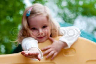 Little smiling girl in the playground.  Focus on hand
