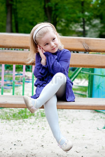 little girl in blue clothes on a bench