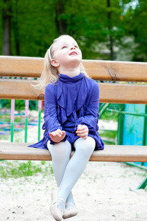 little girl in blue clothes on a bench. Looking up