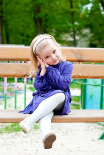 little girl in blue clothes on a bench. Outdoor shot