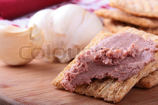 Wheat crackers on a kitchen board with meat paste.