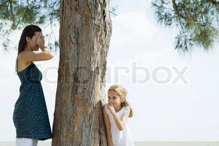 ©Frédéric Cirou/AltoPress/Maxppp ; Two sisters playing hide-and-seek, one covering eyes with hands, the other peeking around tree trunk