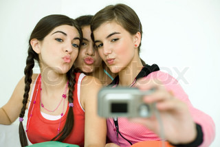 ©Laurence Mouton/AltoPress/Maxppp ; Three young female friends puckering as one takes photo with digital camera