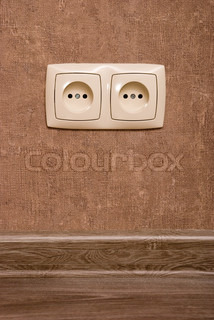 Electric socket on brown wallpaper background