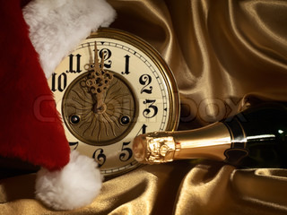New year theme with Champagne, vintage clock and Santa hat over golden drapery