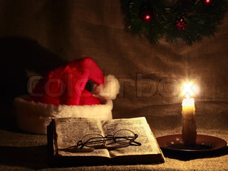 Christmas and New year theme with open Bible, candle, Santa`s hat and garland