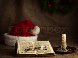 Christmas and New year theme with open Bible, vintage clock, candle, Santa`s hat and garland