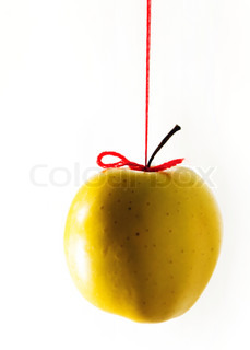 Yellow apple hanging on a red thread