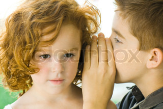 ©Michèle Constantini/AltoPress/Maxppp ; Boy whispering into girl's ear, close-up