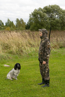 Blonde in camouflage with a gun and russian hunting spaniel.