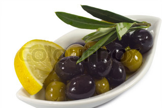Green and black olives in olive oil with olive branch and lemon slice on a plate
