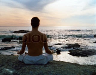 ©Téo Lannié/AltoPress/Maxppp ; Man sitting in lotus position in front of sea, rear view, silhouette