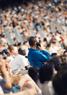 ©Frédéric Cirou/AltoPress/Maxppp ; Man standing in crowd, holding walkie-talkie