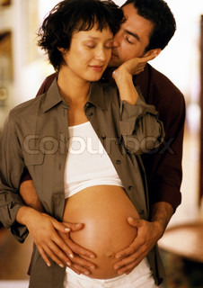 ©John Dowland/AltoPress/Maxppp ; Man touching pregnant woman's stomach from behind, eyes closed, portrait
