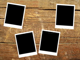 set of four old blank polaroids frames lying on a wood surface