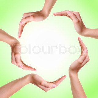 Woman's hands made circle on green background