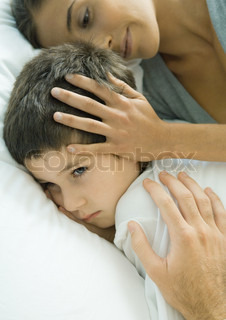 ©Odilon Dimier/AltoPress/Maxppp ; Child lying in bed, parent's hands on head and shoulder
